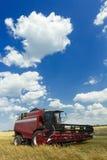 Combine la máquina con el jefe o la cuchilla de corte que se coloca en campo de granja de la avena Fotos de archivo
