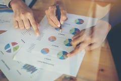 combine las manos de la mujer de negocios que trabajan y que llevan a cabo el gráfico de negocio inf Foto de archivo