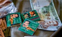 Combine livros e moeda com a foto do ` s de Saddam Hussein neles fotos de stock royalty free