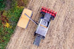 Combine loading corn grain on trailer. Royalty Free Stock Photography