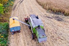 Combine loading corn grain on trailer. Stock Photos