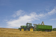 Combine and tractor in barley field Royalty Free Stock Photos