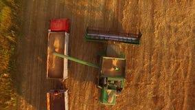 Combine unloads grain into truck. stock footage