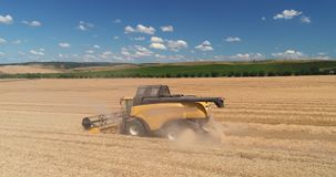 Combine working on harvest agricultural field, aerial drone view stock footage