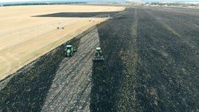 Combineert ploegen en oogsten een massief landbouwgebiedsgebied stock footage