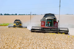 Combines harvesters working on a wheat field. Kharkiv Region, Ukraine - July 25, 2017: Combines harvest wheat on a field in sunny summer day in Kharkiv Region Stock Images