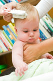 Combing baby. Mother combing her baby girl Royalty Free Stock Image