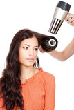 Combing and dry the hair. Hairdresser combing and dry the hair of a woman,  on white background Stock Images