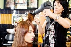 Combing and dry the hair. Hairdresser combing and dry the hair in a salon Royalty Free Stock Image