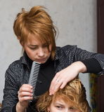 Combing hair. A woman stylist combing another woman's hair Royalty Free Stock Image