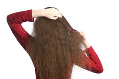 Combing Hair. Woman back with comb combing her brown unruly hair Royalty Free Stock Image