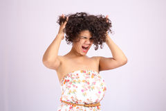 Combing hair. Angry woman combing her long unmanageable unruly problematic hair. Stock Image