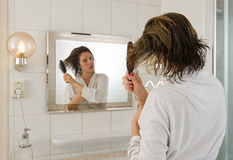 Combing hair in bathroom Stock Photo
