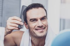 Handsome model combing his hair. Combing. Handsome joyful model expressing cheerful emotions while looking at you and combing his hair Stock Images