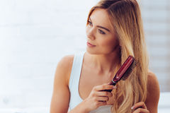 Combing her hair to keep it healthy. Stock Images