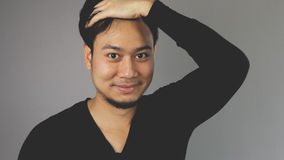 Combing his hair with his hand. An asian guy with black t-shirt stock photos