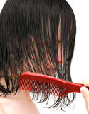 Combing wet hair. Young girl combing her wet hair, side view this time Stock Images