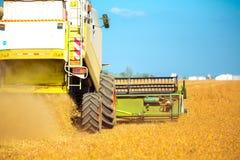 Combini la macchina con la carrozza che raccoglie l'avena sull'azienda agricola Fotografia Stock Libera da Diritti