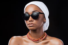 Combining fashion and traditions. Beautiful African woman wearing a headscarf and sunglasses while standing against black background Stock Photography
