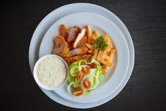 Combo λουρίδων και τηγανητών κοτόπουλου στο μαύρο ξύλο Στοκ φωτογραφία με δικαίωμα ελεύθερης χρήσης