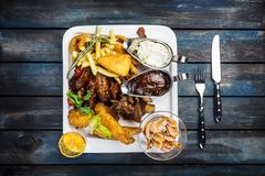 Combo snacks composition with chicken wings, lamb ribs, sausages, fried shrimp, onion rings, nuggets fish and turkeys royalty free stock photos