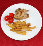 Combo dish. Chicken combo dish with fried potatoes and tomatoes on red tablecloth Stock Image
