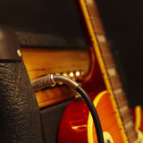 Combo for electric guitar with guitar on the black background. Shallow depth of field, low key, close up. Royalty Free Stock Photography