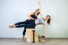 Combo wunda pilates chair woman with instructor. Combo wunda pilates chair women with instructor fitness yoga gym exercise royalty free stock photography