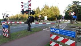 Comboio elétrico de dois andares interurbanos holandês que atravessa a travessia do comboio com barreiras para bloquear o tráfe video estoque