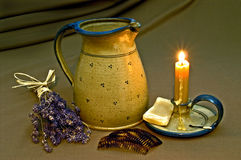 Combs and candle. An arrangement of a jug, a burning candle in a holder, combs, a piece of old soap and a bunch of lavender royalty free stock photography
