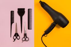 Combs and hairdresser tools on color background top view