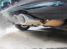 A combustão fumes saindo da tubulação de exaustão preta do carro, conceito da poluição do ar fotografia de stock royalty free