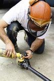 Combustível de derramamento do trabalhador em uma serra de cadeia Imagens de Stock