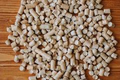Combustible biológico - pequeñas pelotillas de madera sobre la tabla de madera fotografía de archivo