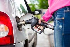Combustible de bombeo de la gasolina de la señora en coche en la gasolinera imagen de archivo