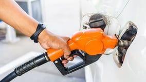 Combustible de bombeo de la gasolina del surtidor de gasolina de la mano del primer en el coche blanco Fotos de archivo