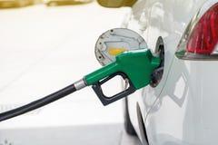 Combustible de gas de aceite rellene y del relleno en la estación Gasolinera - reaprovisionamiento Para llenar la máquina del com fotografía de archivo