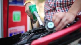 Combustible de relleno de la gasolina de la boca de la bomba de gas del uso del hombre al tanque de motocicleta en la estación de almacen de video
