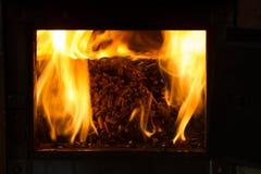 Combustion dans les granules de four du pin Photographie stock libre de droits