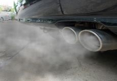 Combustion fumes coming out of black car exhaust pipe, air pollution concept.  stock photography