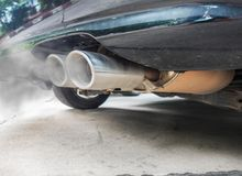Combustion fumes coming out of black car exhaust pipe, air pollution concept.  royalty free stock photography