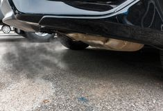 Combustion fumes coming out of black car exhaust pipe, air pollution concept.  royalty free stock photos