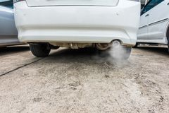 Combustion fumes coming out of car exhaust pipe, air pollution concept.  Stock Photo