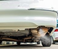 Combustion fumes coming out of car exhaust pipe, air pollution concept.  Royalty Free Stock Photography