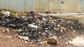 Combustion residue with trash on the ground stock images
