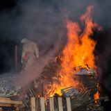Combustione bianca del burattino nel fuoco di accampamento di legno con le alte fiamme Immagini Stock