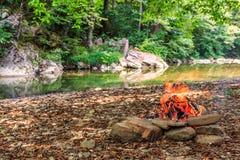 Combustione del fuoco di accampamento sulla sponda del fiume pietrosa nel paesaggio scenico di giorno soleggiato di estate della  fotografia stock