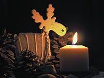 Combustione della candela di Natale con le alci di legno e delle pigne Fotografie Stock