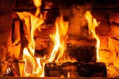 Combustione della legna da ardere nelle ustioni del fuoco nel camino Il forno del mattone dà il calore ed il calore dai ceppi bru fotografia stock libera da diritti