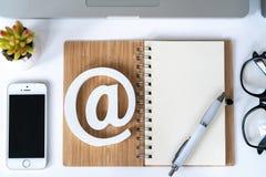 Comcept d'email Contactez-nous pour le retour Bureau avec le bloc-notes, le smartphone, les verres et le symbole d'email Vue sup? photo stock